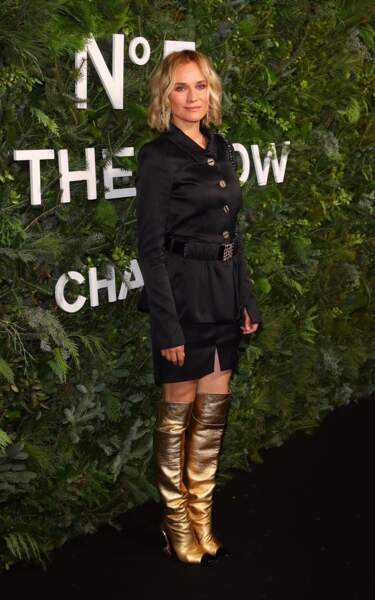 Diane Kruger complète son total look noir avec une paire de bottes plissées dorées signée Chanel.
