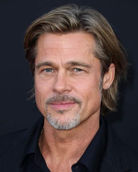 les cheveux mi longs et coiffés sur le côté de Brad Pitt