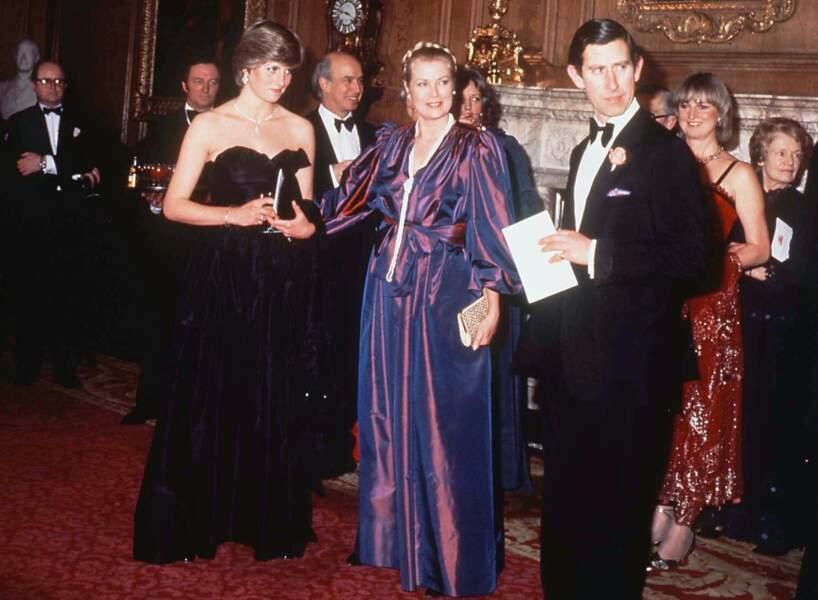 La princesse Diana dans une robe bustier noire, dessinée par David et Elizabeth Emanuel, avec Grace Kelly et le prince Charles, lors d'un gala à Londres en 1981.