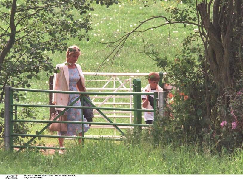 La princesse Diana dans une robe à imprimé floral bleu ciel, avec son fils le prince Harry dans les jardins de l'école Ludgrove en 1996.