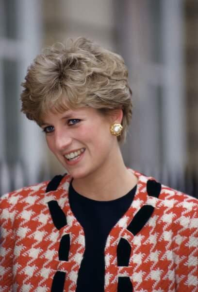 La princesse Diana, avec une veste à imprimé pied de poule rouge et crème signée Moschino, lors de la visite d'un hôpital à Londres en 1992.