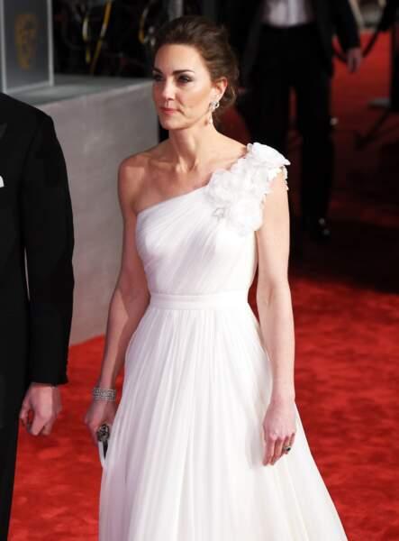 Kate Middleton dans une robe de soirée blanche à épaule dénudée Alexander McQueen, lors de la cérémonie des BAFTA Awards au Royal Albert Hall à Londres, le 10 février 2019.