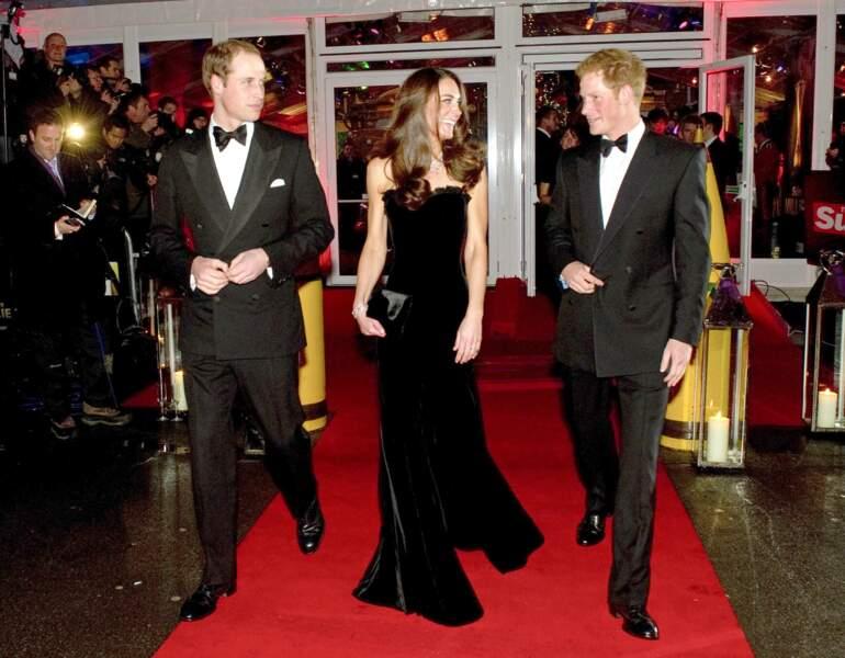"""Kate Middleton, accompagnée du prince William et du prince Harry,  dans une robe bustier noire Alexander McQueen, lors de la cérémonie """"The Sun Military Awards"""" à Londres, le 19 décembre 2011."""