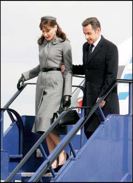 Carla Bruni fait un sans faute à son arrivée à l'aéroport d'Heathrow au Royaume-Uni dans un style à la Jackie Kennedy avec un bibi assorti à son manteau gris ceinturé. A ses côtés, Nicolas Sarkozy apparaît fier.