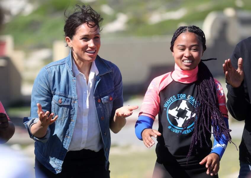 """Meghan Markle à la rencontre des membres de """"Waves for Change"""" un organisme de bienfaisance qui travaille avec les surfeurs locaux sur la plage de Monwabisi au Cap. Loin du Royaume, elle a choisi une tenue très décontractée pour l'occasion, qui n'a pas manqué de faire jaser. Une duchesse en veste en jean, du jamais vu !"""