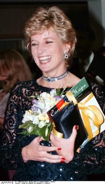 La princesse Diana dans une robe bleue marine, en dentelle brodée de sequins en 1996. Elle porte cette robe similaire à celle de Meghan Markle lors d'un concert de Pavarotti à Cardiff.