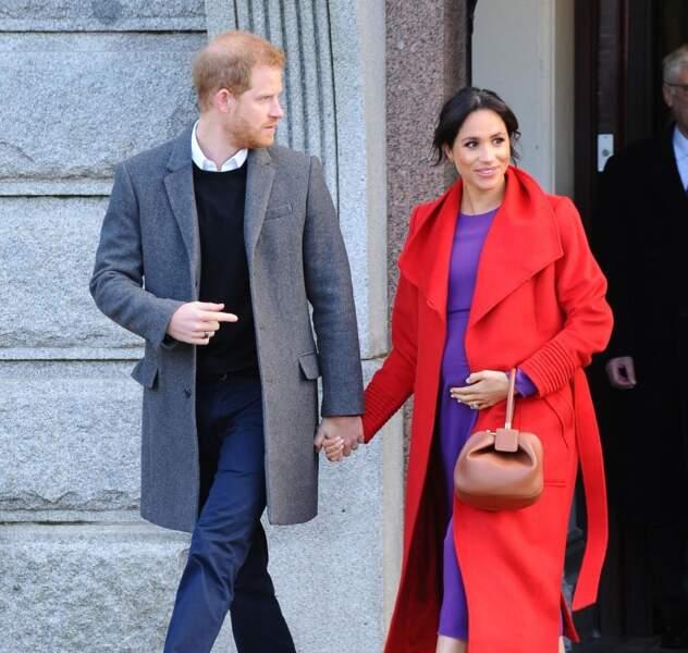 La duchesse Meghan Markle fait sensation à Birkenhead le 14 janvier 2019 en mixant cette robe violette à un manteau rouge.