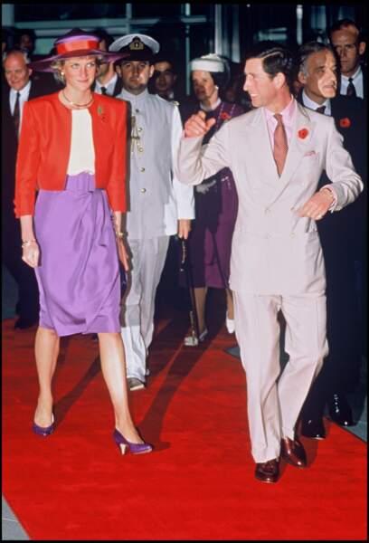 La princesse Lady Di est aux côtés du prince Charles lors d'une visite à Hong kong. Mélanger le violet et le rouge est un choix osé que Meghan Markle n'a pas hésité à reproduire.