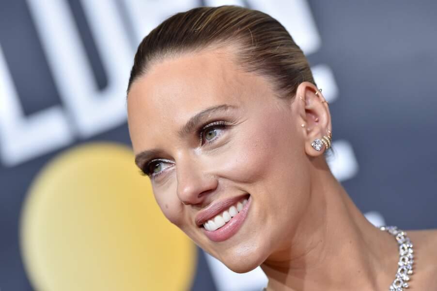 Maquillage lumineux et cheveux plaqués en arrière et noués en un petit chignon, Scarlett Johansson est sublime.
