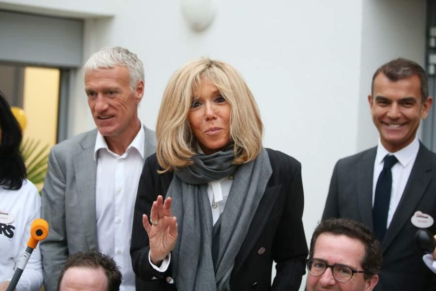 Brigitte Macron chic en blouse blanche col lavallière, veste longue et étole grise.