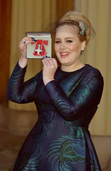 19 décembre 2013 : La chanteuse Adele pose dans une tenue très classe avec sa médaille MBE. Le succès toujours au beau fixe, elle est décorée par le prince Charles pour ses talents musicaux lors d'une cérémonie au Palais de Buckingham.