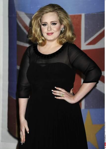 2012 : Adele pendant les Brit Awards 2012 à l'Arena de Londres. Niveau look, Adele aime travailler le total look noir, serré à la taille. Elle a changé de couleur de cheveux, mise sur le volume et un maquillage plus prononcé.