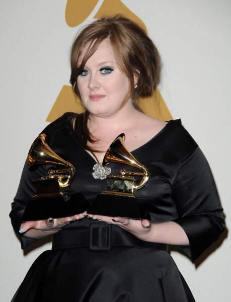 """Février 2009 : Adele remporte deux trophées lors de la 51e cérémonie des Grammy Awards à Los Angeles. La chanteuse de """"Rolling in the deep"""" commence à porter des coiffures rétro, et ce fameux trait de liner noir sur les yeux."""