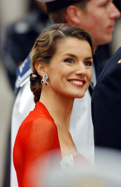Mai 2004 : Sublime, Letizia d'Espagne est rayonnante dans cette robe rouge. Elle porte un chignon bas mis en valeur par ses boucles d'oreilles.