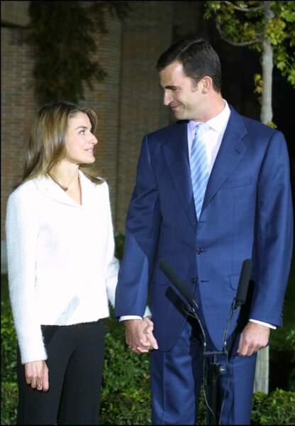 Novembre 2003 : A 33 ans, Letizia Ortiz, apparaît pour la première fois main dans main avec Felipe d'Espagne face à la presse au Palais Zarzuela de Madrid. Cheveux châtains et blazer pantalon, la princesse joue la simplicité pour cette première présentation.