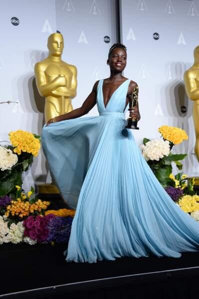 Lupita Nyong'o porte une robe décolletée Prada lorsqu'elle remporte l'Oscar de la meilleur actrice dans un second rôle lors de la 86e cérémonie en 2014 .
