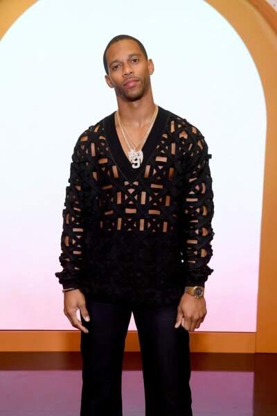 Victor Cruz sexy en noir, dans un pull col v à moitié cousu et aux motifs originaux.
