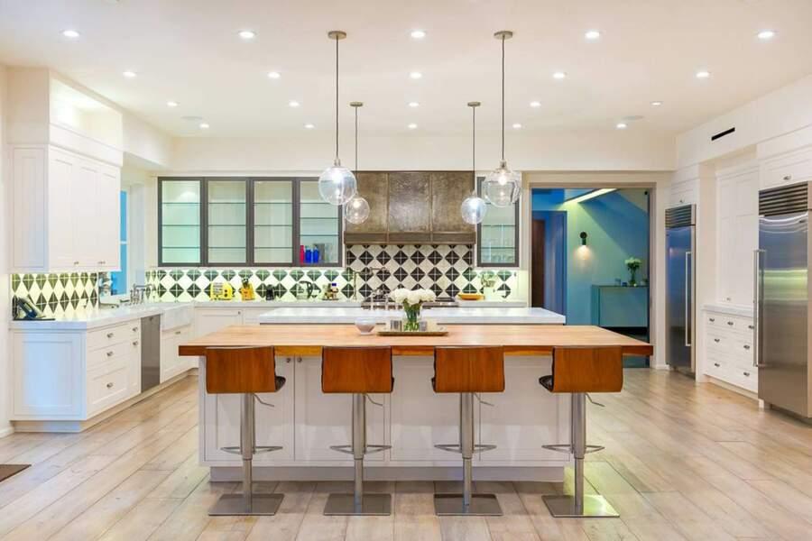 L'élégante cuisine américaine dispose de deux ilots recouverts de marbre et d'un plancher en bois