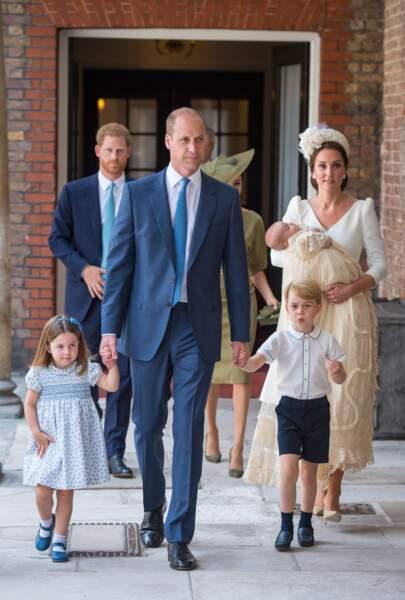 Le prince William et son épouse, Kate Middleton suivis de près par le prince Harry et Meghan Markle à l'occasion du baptême du prince Louis le 9 juillet 2018.