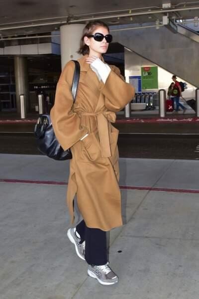 Kaia Gerber porte un manteau en cachemire camel et une paire de New Balance 574 à son arrivée à l'aéroport de LAX