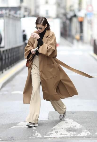 Kaia Gerber porte le pantalon large fluide avec des baskets et un long manteau.