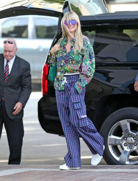 Heidi Klum mixe ici un pantalon large rayé et une chemise à fleurs.