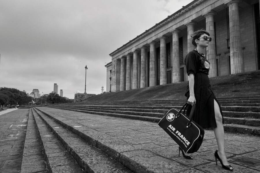 Solaires Optic 2000, collier Louis Vuitton, sac de voyage Bowling Air France, escarpins Bettina Vermillon. Tee-shirt en coton et jupe en soie Chloé.