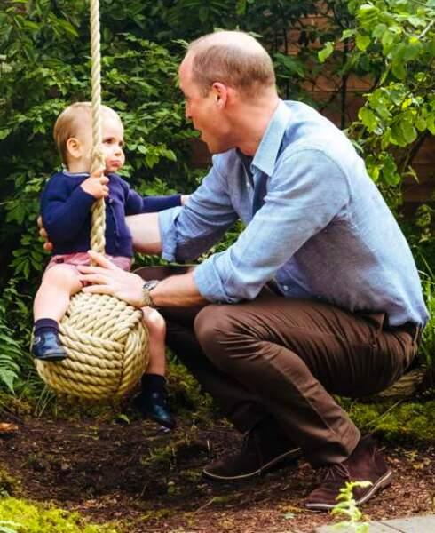 Louis sur la balançoire, avec son papa, le prince William, veillant sur lui.