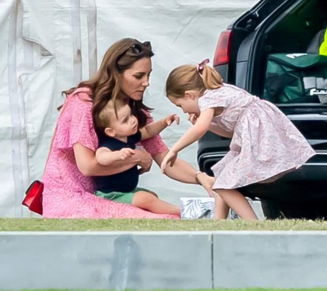 Le prince Louis, avec sa maman et sa grande soeur Charlotte, lors d'un match de polo de bienfaisance King Power Royal Charity Polo Day à Wokinghan, en juillet 2019.