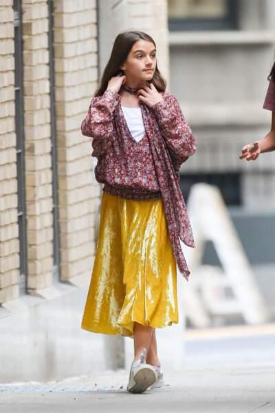 Suri Cruise  : une vraie fille en jupe plissée dorée et blouse fleurie.