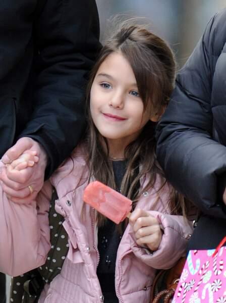 Suri Cruise, souriante, deguste un esquimau alors qu'elle se promene avec sa nounou et son garde du corps a New York, le 11 decembre 2013.