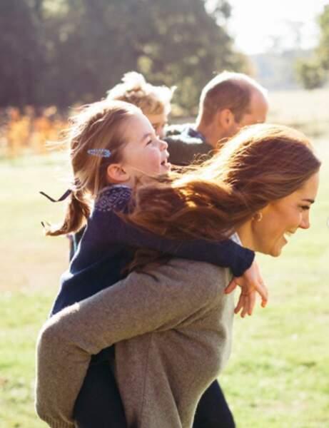 Charlotte sur le dos de sa maman, et George sur le dos de son papa, dans leur jardin. Un moment de complicité adorable.