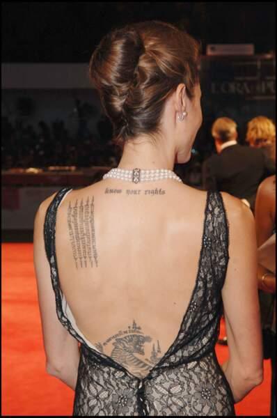Angelina Jolie multiplie les tatouages avec un tigre en bas du dos et des slogans politiques sur la nuque.