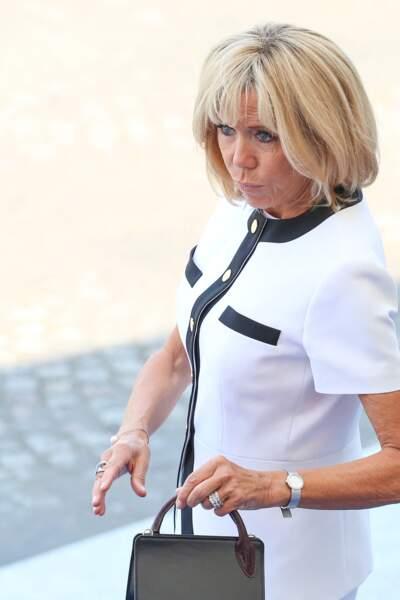 Afin de parfaire son look très Jackie Kennedy ce 14 juillet 2018, Brigitte Macron avait choisi un petit sac carré en cuir noir de la maison Jacquemus. A son poignet : la montre D, modèle satiné, de Dior.