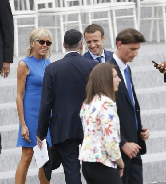 """Lunettes de soleil, micro-robe bleu cobalt sans manches et talons vertigineux Louis Vuitton : Brigitte Macron met peut-être un peu trop en valeur sa silhouette de """"sexy sexa"""", ce 14 juillet 2016."""