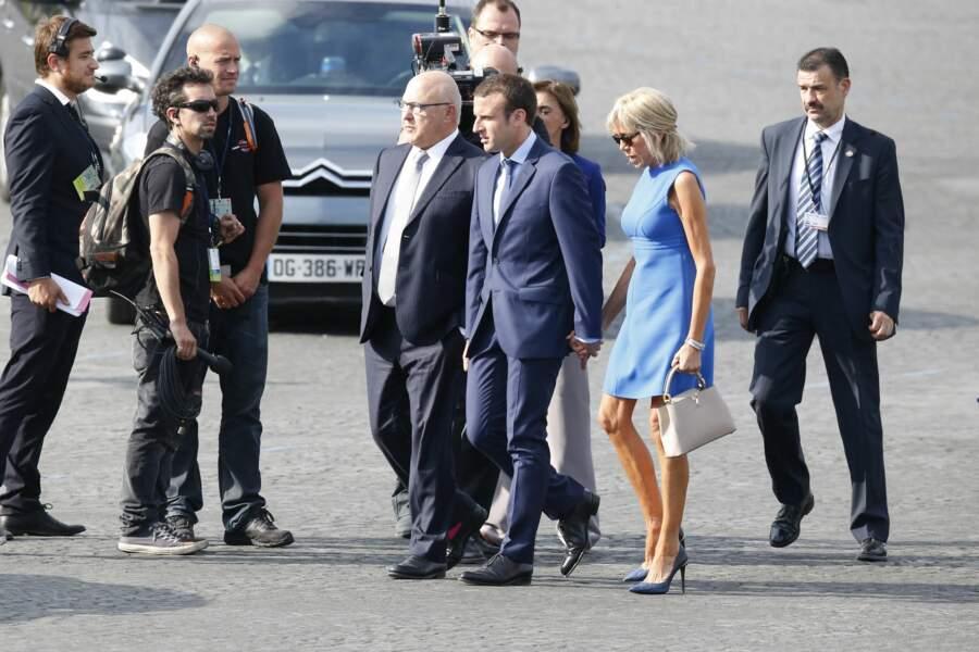 Brigitte et Emmanuel Macron en route vers la tribune présidentielle pour le défilé du 14 juillet 2015. C'est la première fois que le couple est photographié à cette occasion. Un an plus tôt, Emmanuel Macron, secrétaire général adjoint de l'Elysée, a été nommé ministre de l'Economie.
