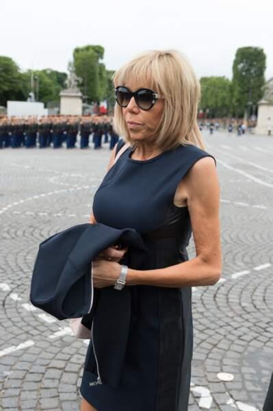 Ce 14 juillet 2016, Brigitte Macron n'est pas encore rodée aux usages et conventions : si elle fait déjà sensation dans une robe sans manches mais avec empiècements de cuir Louis Vuitton, l'épouse d'Emmanuel Macron ose des lunettes de soleil un peu trop bling.
