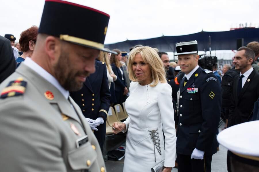 Détail remarqué sur la robe à manches longues de Brigitte Macron ce 14 juillet 2019 : ses laçages argentés au niveau de hanches, raccord avec sa pochette.
