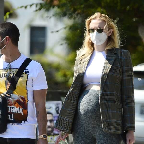 Malgré le masque, Sophie Turner enceinte de son premier enfant et chic avec une veste à carreaux et un sac griffé.