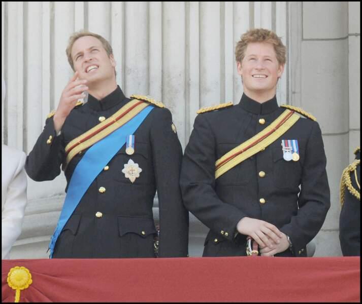 Difficile de toujours garder son sérieux ! William tente de garder son calme quand Harry pouffe de rire lors de la revue des troupes à Londres sur le balcon de Buckingham Palace. Attention, la reine veille...