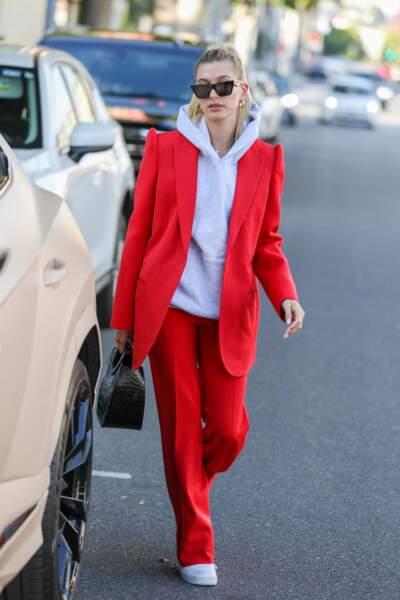 Hailey Baldwin Bieber associe un costume rouge chic et un sweat à capuche gris pour sortir.