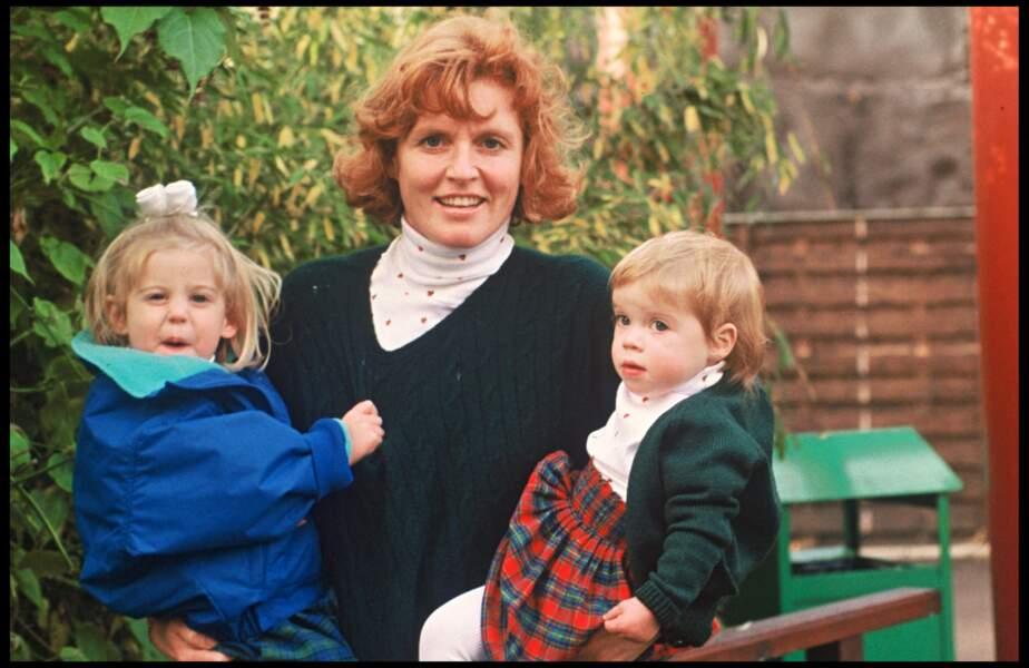 Sarah Ferguson tout sourire avec ses deux filles Eugenie et Beatrice affectueusement portées dans ses bras en 1991.