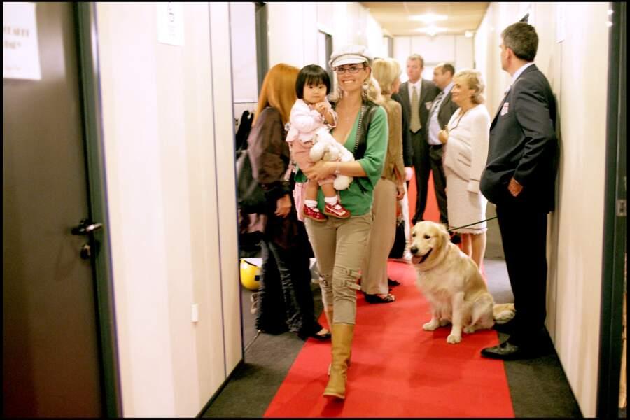 """Jade Hallyday, dans les bras de Laeticia Hallyday, sur le plateau de """"+ de vie"""", pour l'association de Bernadette Chirac, en octobre 2005."""