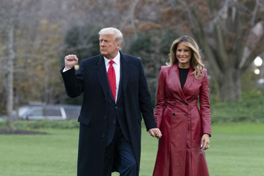 Melania Trump souriante, vêtue avec un long manteau en cuir rouge, au côté de son mari.