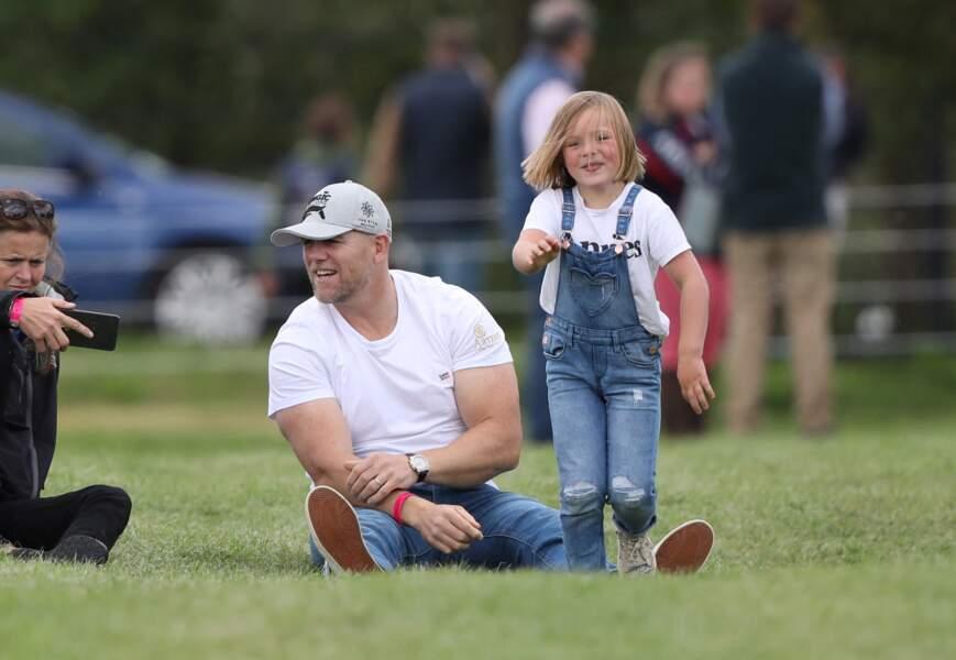 Mike Tindall joue avec sa fille Mia dans l'herbe pendant que sa femme Zara Tindall participe à la compétition Land Rover Burghley Horse Trials à Stamford, le 7 septembre 2019.