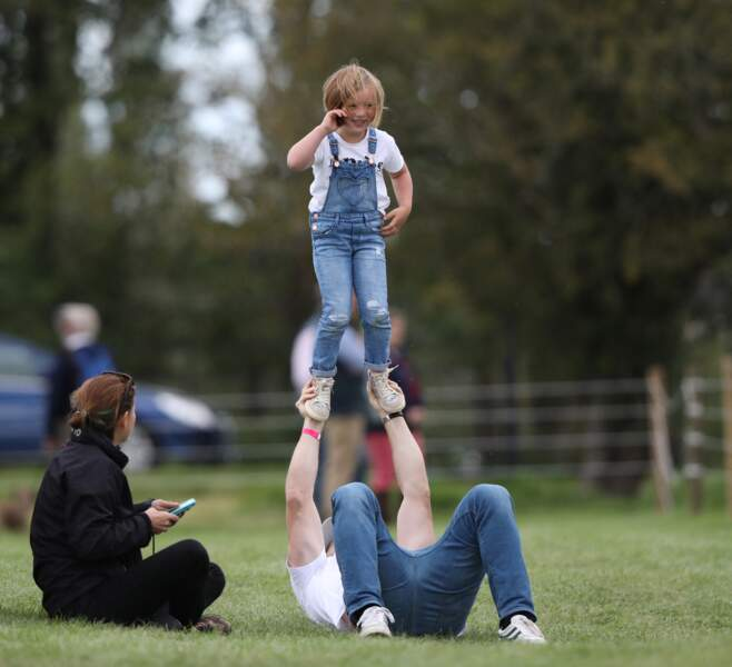 Mike Tindall s'amuse avec sa fille Mia dans l'herbe alors que sa femme Zara Tindall participe à la compétition Land Rover Burghley Horse Trials à Stamford, le 7 septembre 2019.