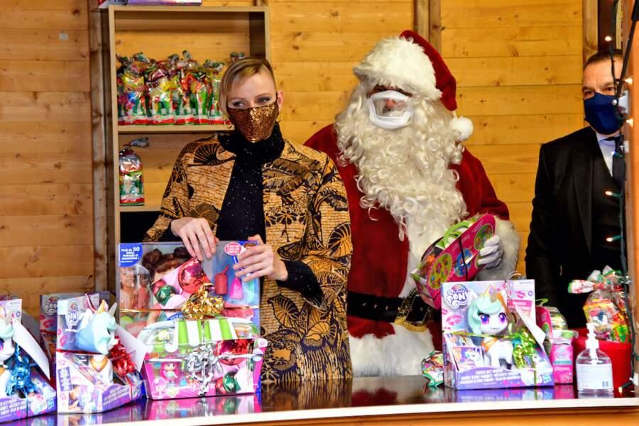 Alors que le Père Noël est caché sous sa longue barbe et son bonnet, la princesse Charlène arbore un look half hawk, lors du Noël de la principauté