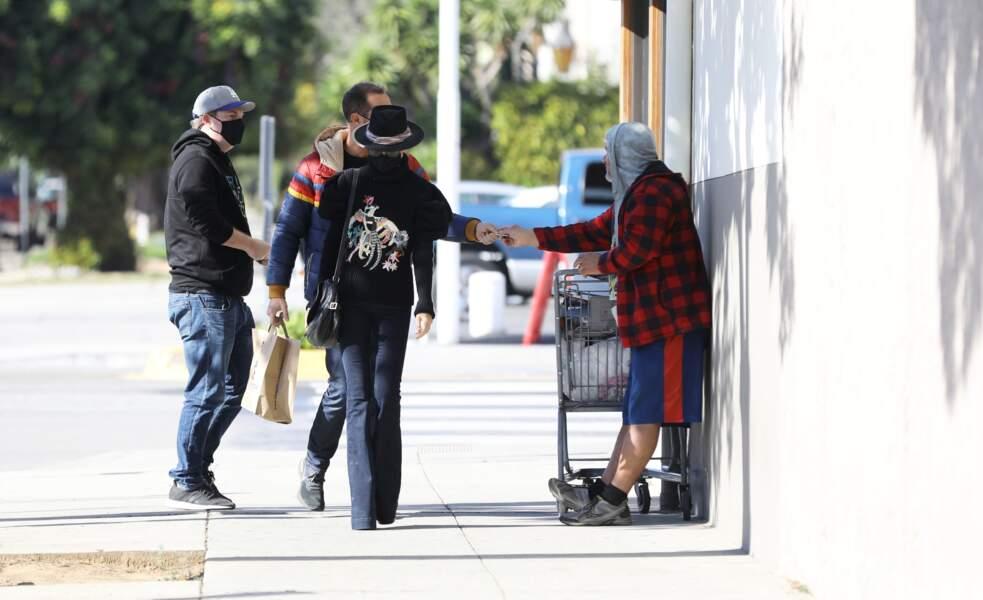 Lors d'une promenade avec sa soeur Laeticia Hallyday dans les rues de Los Angeles, Grégory Boudou donne de l'argent à un SDF. Le 24 janvier 2021.