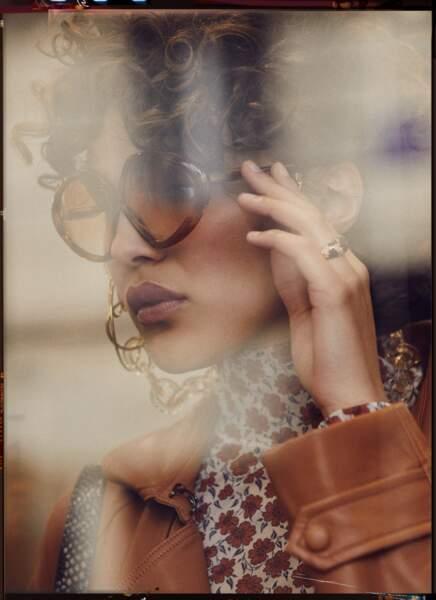 Tendances cette saison, les lunettes vintage Victoria Beckham sont associées au trench en cuir Suncoo, au sous pull imprimé Levi's. La mannequin porte une chaîne Emmanuelle Khanh et une bague Ti Sento Milano.