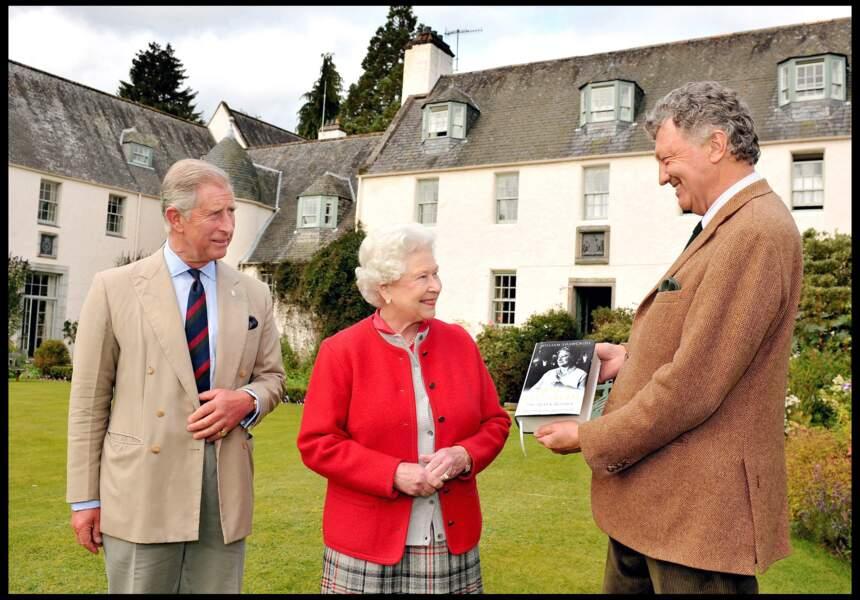 La reine Elizabeth II reçoit le premier exemplaire de sa biographie des mains de l'auteur William Shawcross en présence du prince Charles, en septembre 2009